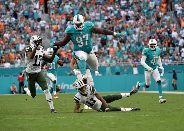 <p>Miami Dolphins defensive tackle Jordan Phillips (97) leaps over New York Jets wide receiver Robby Anderson (11) after making an interception during the second half at Hard Rock Stadium. The Dolphins won 27-23. Mandatory Credit: Steve Mitchell-USA TODAY Sports </p>