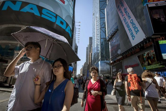 A couple shade themselves beneath an umbrella walking past the Nasdaq Market site in New York's Times Square August 27, 2014. REUTERS/Brendan McDermid (UNITED STATES - Tags: ENVIRONMENT BUSINESS)