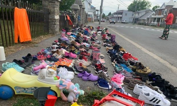 The shoes symbolize the 215 lives lost, many of which are not documented.