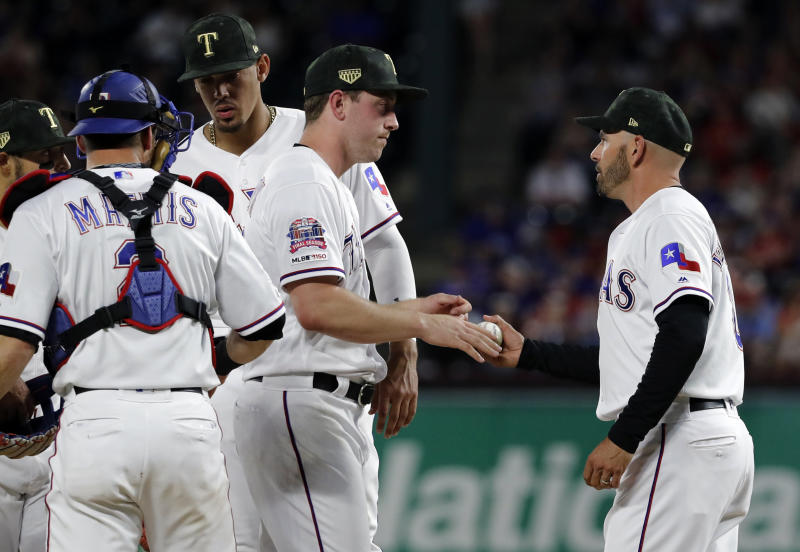 Texas Rangers relief pitcher Adrian Sampson turns over the ball o manager Chris Woodward, right, as Jeff Mathis (2) and Ronald Guzman, rear, stand on the mound in the seventh inning of a baseball game against the St. Louis Cardinals in Arlington, Texas, Friday, May 17, 2019. (AP Photo/Tony Gutierrez)