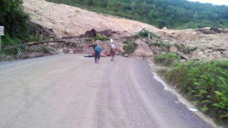 A supplied image shows locals inspecting a landslide and damage to a road located near the township of Tabubil after an earthquake that struck Papua New Guinea's Southern Highlands, February 26, 2018. Jerome Kay/Handout via REUTERS