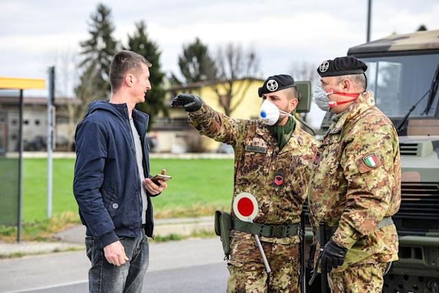 Soldiers wearing protective respiratory masks gesticulate at the border of the isolated small town of Castiglione d'Adda in Italy as measures are taken to contain the outbreak of coronavirus. (Piero Cruciatti/Sipa USA)