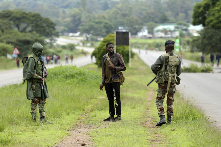 Soldiers patrol the streets as protestors gather during a demonstration over the hike in fuel prices in Harare, Zimbabwe, Tuesday, Jan. 15, 2019. A Zimbabwean military helicopter on Tuesday fired tear gas at demonstrators blocking a road and burning tires in the capital on a second day of deadly protests after the government more than doubled the price of fuel in the economically shattered country. (AP Photo/Tsvangirayi Mukwazhi)