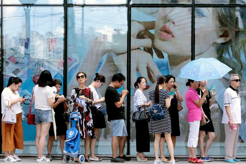 FILE PHOTO: People queue outside of a newly opened duty free shop in Shanghai