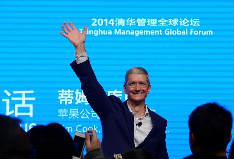Apple CEO Tim Cook waves as he attends a talk in Beijing