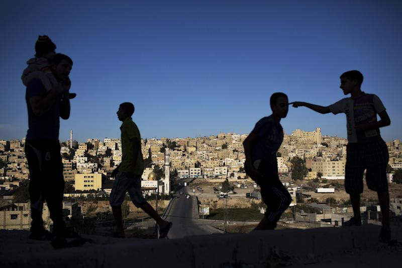 In this Monday, Oct. 21, 2013 photo, Jordanian youths play on a hill on the outskirts of Zarqa, Jordan's industrial center where thousands of Syrian refugees are living, northeast of the capital Amman. More than 420,000 Syrian refugees have settled in Jordan's cities, struggling for survival on U.N. foods stamps and straining the meager resources of a country that absorbed millions of exiles from the region's hotspots in the past. (AP Photo/Manu Brabo)