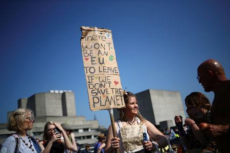 A climate change activist holds a sign during the Extinction Rebellion protest in London, Britain April 21, 2019. REUTERS/Hannah McKay