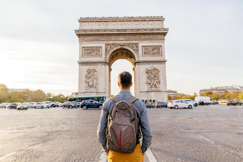 Tourist with backpack walking towards Arc de Triomphe in Paris, France