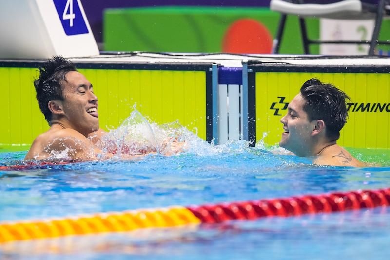 Singapore swimmer Joseph Schooling (right) is being congratulated by compatriot Quah Zheng Wen after winning the men's 100m butterfly gold. (PHOTO: SNOC/Andy Chua)