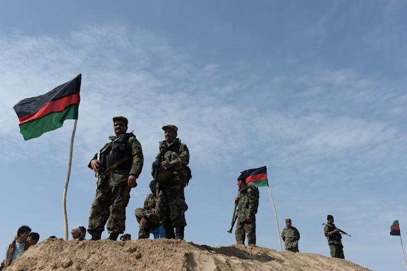 Afghan security personnel keep watch on the outskirts of Kunduz province in 2014