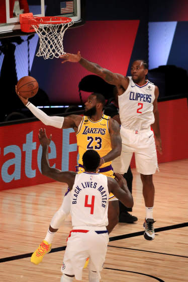 LeBron James #23 of the Los Angeles Lakers goes for a lay up against Kawhi Leonard.