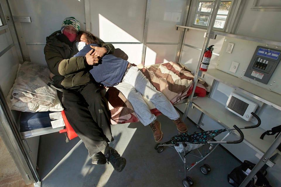 Chris Foss, left, and Tiecha Vannoy embrace after moving into a new pod set up by the city in the Old Town district in Portland, Ore., on Dec. 8, 2020. The pandemic has caught homeless service providers in a crosscurrent: Demand is high, but their ability to provide services is constricted.