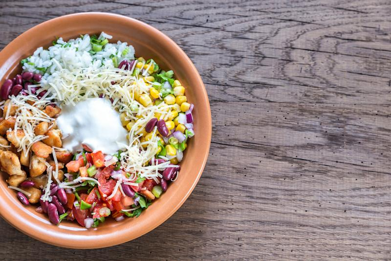 An overhead view of a burrito bowl sitting on a wooden table.