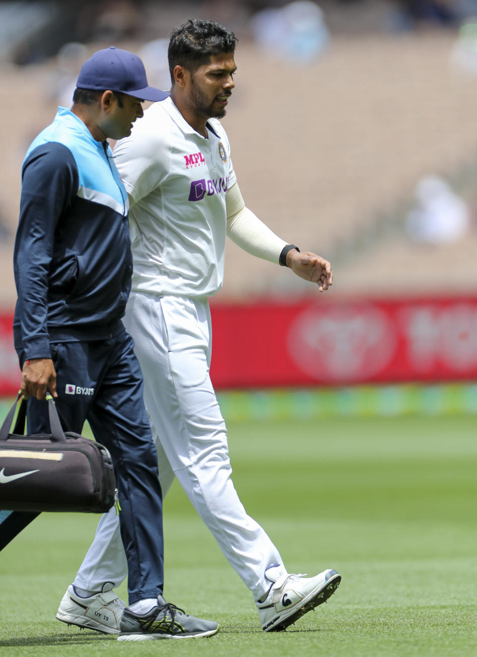India's Umesh Yadav, right, walks from the field for treatment during play on day three of the second cricket test between India and Australia at the Melbourne Cricket Ground, Melbourne, Australia, Monday, Dec. 28, 2020. (AP Photo/Asanka Brendon Ratnayake)