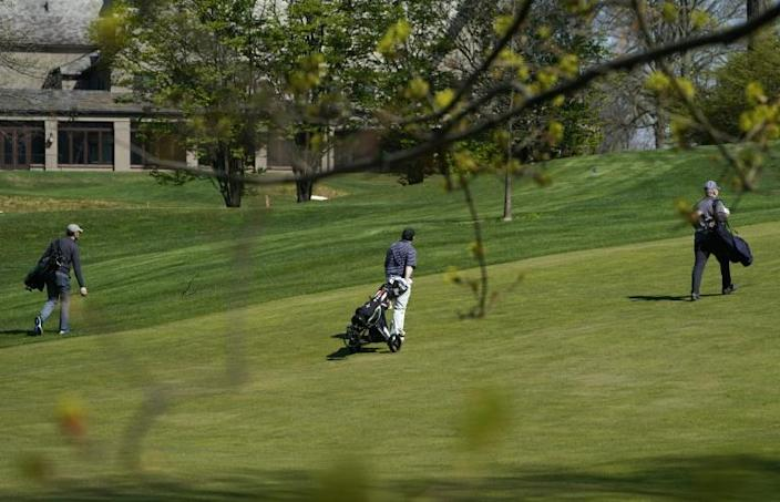 Golfers are seen on the fairway at the private Quaker Ridge Golf Club in Scarsdale, New York after the state hardest-hit by COVID-19 altered its guidance by saying that golf courses could open with some restrictions (AFP Photo/TIMOTHY A. CLARY)