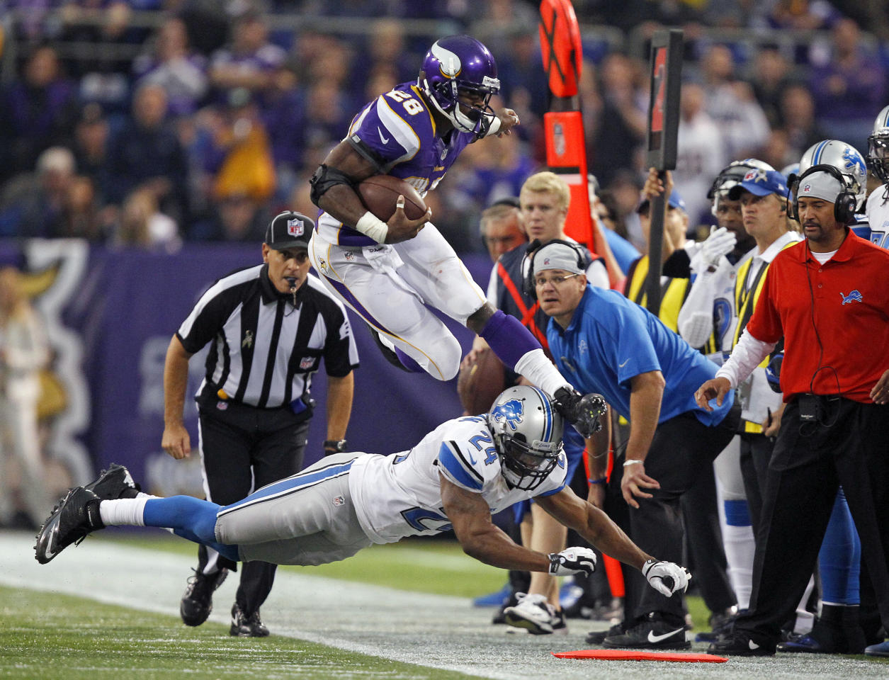 Minnesota Vikings running back Adrian Peterson (28) leaps over Detroit Lions safety Erik Coleman (24) during the second half of their NFL football game in Minneapolis, November 11, 2012. REUTERS/Eric Miller (UNITED STATES - Tags: SPORT FOOTBALL TPX IMAGES OF THE DAY)