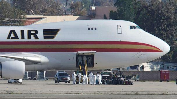 PHOTO: In this Jan. 29, 2020, file photo, personnel in protective clothing approach an aircraft used to evacuate government employees and other Americans from Wuhan, China, after it arrived at March Air Reserve Base in Riverside County, Calif. (Mike Blake/Reuters, FILE)