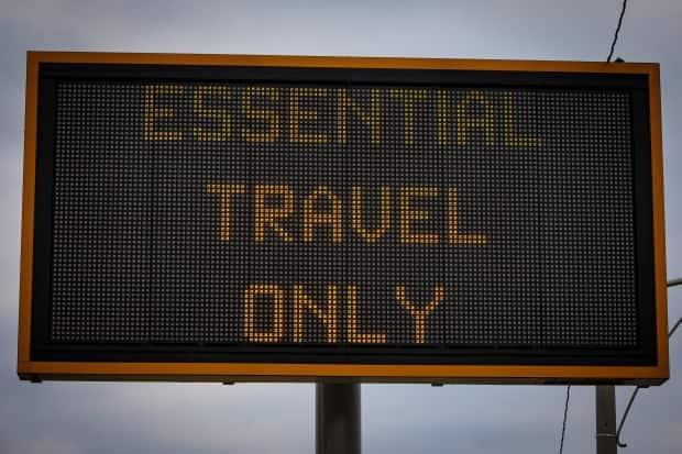A road sign in Toronto in January informs drivers to travel only for essential reasons. Ontario remains in a state of emergency that includes orders to stay at home except for essential trips. (Evan Mitsui/CBC - image credit)