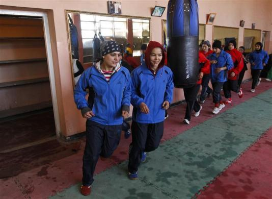 Sadaf Rahimi (L) jogs during a training session inside a boxing club in Kabul February 13, 2012.