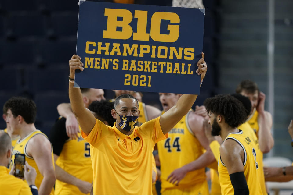 FILE - Michigan coach Juwan Howard holds a championship sign after the team's win over Michigan State in an NCAA college basketball game in Ann Arbor, Mich., in this Thursday, March 4, 2021, file photo. Michigan's Juwan Howard is coach of the year in the Big Ten, announced Tuesday, March 9, 2021. (AP Photo/Carlos Osorio, File)