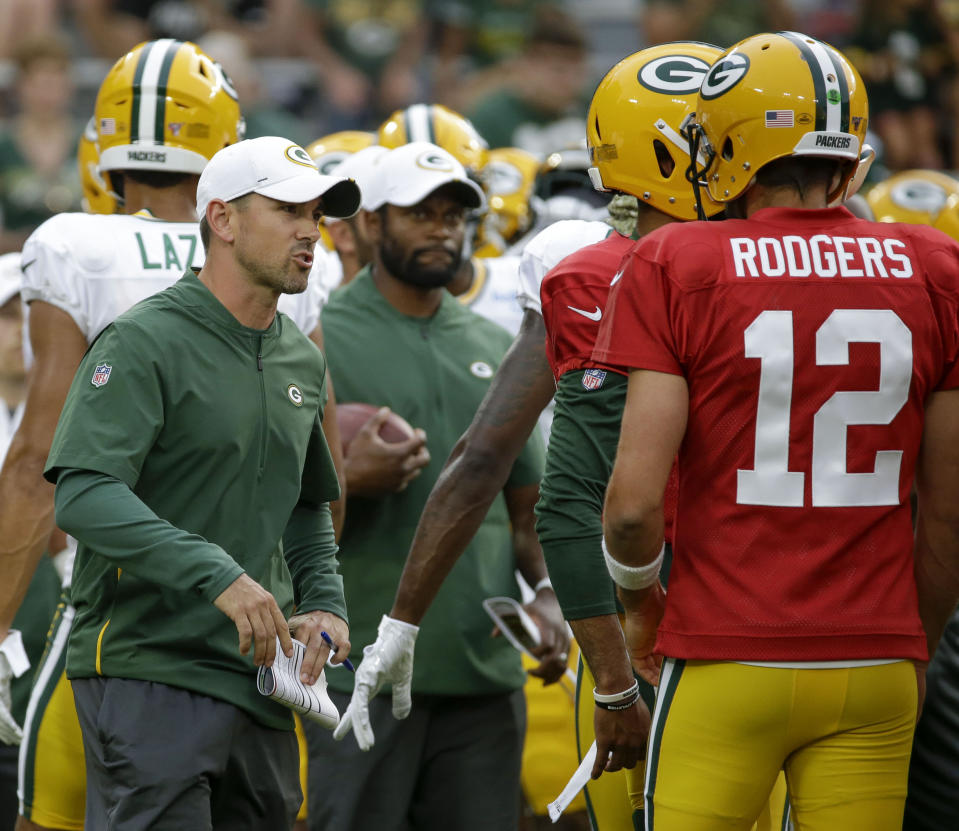 Green Bay Packers coach Matt LaFleur, left, talks with quarterback Aaron Rodgers during the NFL football team's Family Night practice Friday Aug 2, 2019, in Green Bay, Wis. (AP Photo/Mike Roemer)