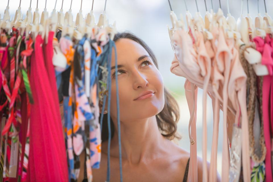 Young woman dreamily looks at bikinis in the store
