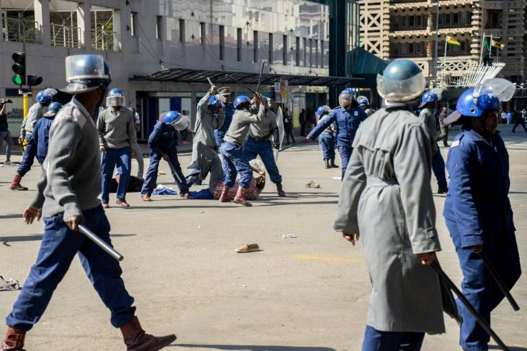 Police beat a protester in a public square in Zimbabwe's capital Harare (AFP Photo/Zinyange Auntony)