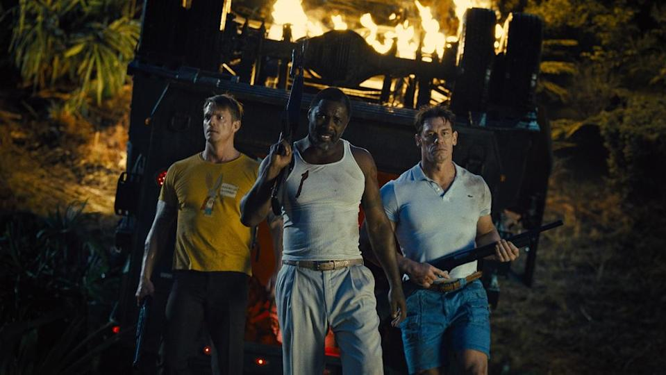 Rick Flagg (Joel Kinnaman), Bloodsport (Idris Elba), and Peacemaker (John Cena) in casual clothes, carrying guns, walking away from a fiery building, in The Suicide Squad.