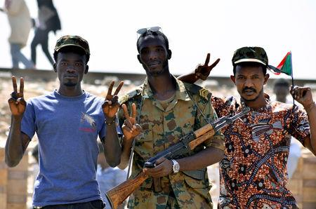 A Sudanese military officer and demonstrators gesture in celebration after Defence Minister Awad Ibn Auf stepped down as head of the country's transitional ruling military council, as protesters demanded quicker political change, near the Defence Ministry in Khartoum, Sudan April 13, 2019. REUTERS/Stringer