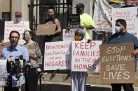 People from a coalition of housing justice groups hold signs protesting evictions during a news conference outside the Statehouse, Friday, July 30, 2021, in Boston. (AP Photo/Michael Dwyer)