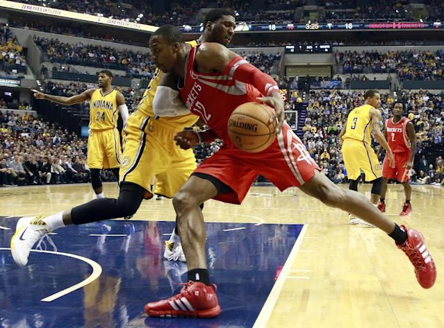 Houston Rockets center Dwight Howard (12) pushes into Indiana Pacers center Roy Hibbert while driving to the basket in the first half of an NBA basketball game in Indianapolis, Friday, Dec. 20, 2013. (AP Photo/R Brent Smith)