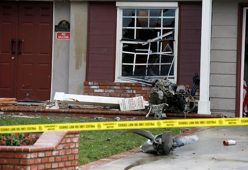 A propeller of a small plane sits on the front of a house after it crashed into the residential neighborhood of Yorba Linda, Calif., Feb. 3, 2019. (Photo: Alex Gallardo/AP)