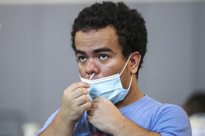 RANCHO CUCAMONGA, CA - AUGUST 20: Jorge Morales, 18, collects nasal specimen by self swabbing at Community COVID-19 testing site held by San Bernardino County Department of Public Health at Rancho Sports Center on Thursday, Aug. 20, 2020 in Rancho Cucamonga, CA. (Irfan Khan / Los Angeles Times)