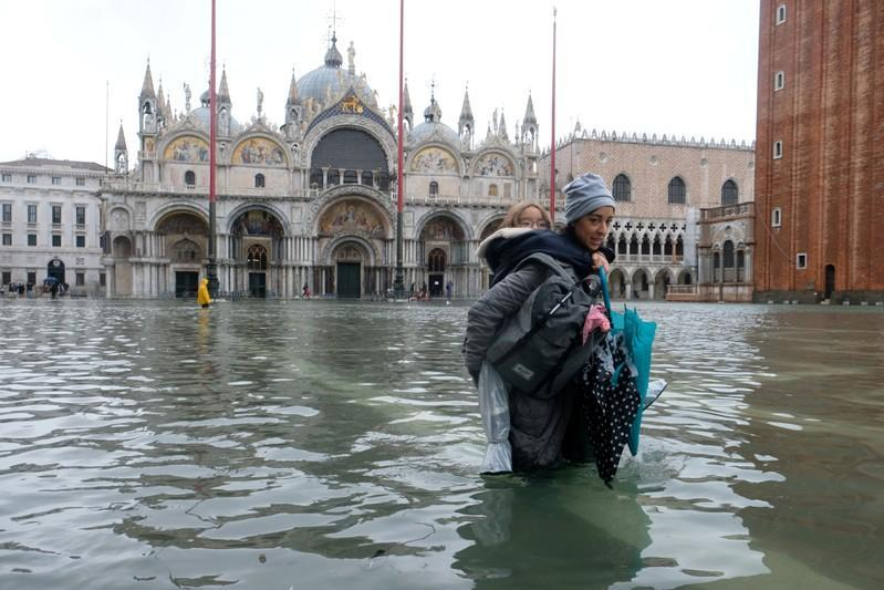 A woman carrying a child on her back wades in the flooded St. Mark's Square in Venice, Italy