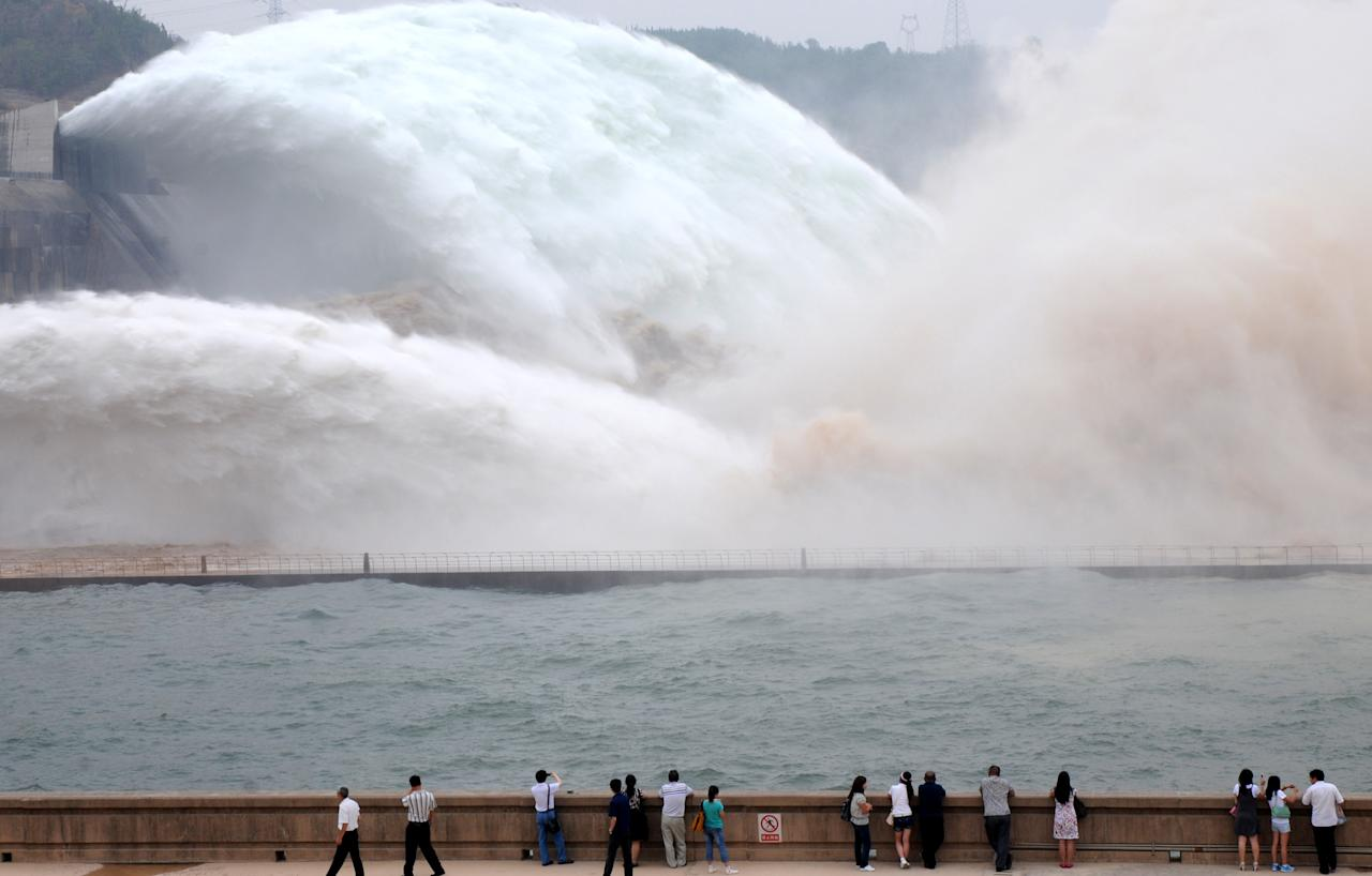 In this photo released by China's Xinhua News Agency, tourists look at the torrents gushing out from the Xiaolangdi Reservoir on the Yellow River, at the reservoir's viewing platform, in Jiyuan, central China's Henan Province, Tuesday, June 21, 2011. The Yellow River Flood Control and Drought Relief Headquarters launched on Sunday a 20-day operation to discharge water from three reservoirs, namely Wanjiazhai, Sanmenxia and Xiaolangdi, in a bid to clear up the sediment in the river, Xinhua said. (AP Photo/Xinhua, Miao Qiunao) NO SALES