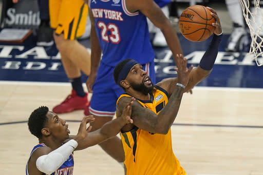 New York Knicks guard RJ Barrett, left, defends as Utah Jazz forward Royce O'Neale, right, lays the ball up in the second half during an NBA basketball game Tuesday, Jan. 26, 2021, in Salt Lake City. (AP Photo/Rick Bowmer)