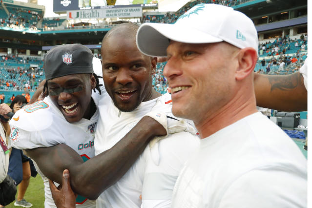 Miami Dolphins defensive back Chris Lammons, left, hugs head coach Brian Flores, center, after an NFL football game against New York Jets, Sunday, Nov. 3, 2019, in Miami Gardens, Fla. (AP Photo/Wilfredo Lee)