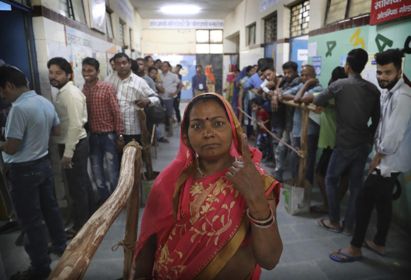 A woman displays indelible ink mark on her finger after casting her vote as others wait in queue in New Delhi, India, Sunday, May 12, 2019. Indians are voting in the next-to-last round of 6-week-long national elections, marked by a highly acrimonious campaign with Prime Minister Narendra Modi flaying the opposition Congress party rival Rahul Gandhi's family for the country's ills. (AP Photo/Manish Swarup)