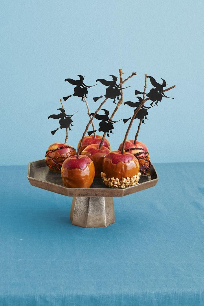 """<p>Turn a basic caramel apple into a Halloween-worthy dessert with sticks and <a href=""""https://go.redirectingat.com?id=74968X1596630&url=https%3A%2F%2Fwww.orientaltrading.com%2Fhalloween-silhouette-decorating-kit-a2-13603146.fltr&sref=https%3A%2F%2Fwww.womansday.com%2Ffood-recipes%2Ffood-drinks%2Fg2586%2Fhalloween-desserts%2F"""" rel=""""nofollow noopener"""" target=""""_blank"""" data-ylk=""""slk:witch cut-outs"""" class=""""link rapid-noclick-resp"""">witch cut-outs</a>.</p><p><a href=""""https://www.womansday.com/food-recipes/food-drinks/recipes/a11045/caramel-apples-recipe-122425/"""" rel=""""nofollow noopener"""" target=""""_blank"""" data-ylk=""""slk:Get the Caramel Apples recipe."""" class=""""link rapid-noclick-resp""""><strong><em>Get the Caramel Apples recipe.</em></strong></a></p>"""