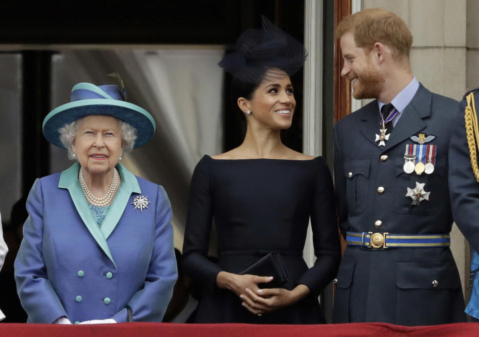 """FILE - In this Tuesday, July 10, 2018 file photo Britain's Queen Elizabeth II, and Meghan the Duchess of Sussex and Prince Harry watch a flypast of Royal Air Force aircraft pass over Buckingham Palace in London. As part of a surprise announcement distancing themselves from the British royal family, Prince Harry and his wife Meghan declared they will """"work to become financially independent"""" _ a move that has not been clearly spelled out and could be fraught with obstacles. (AP Photo/Matt Dunham, File)"""
