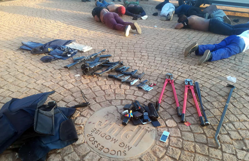 In this photo made available by the South African Police Services (SAPS), confiscated arms and ammunition, foreground, and arrested suspects, background, lay face-down at a church in Zuurbekom, near Johannesburg, Saturday, July 11, 2020. Police in South Africa say five people are dead and more than 40 have been arrested after an early-morning hostage situation at a church near Johannesburg. (South African Police Services via AP)