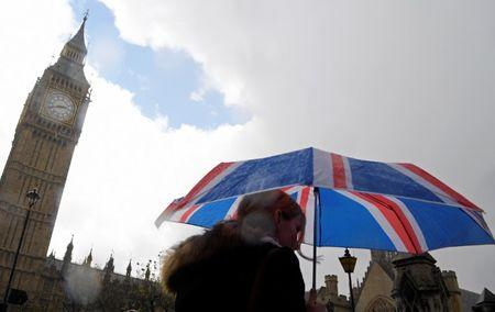 A woman carries a British union flag design umbrella as she walks past the Houses of Parliament in London, Britain
