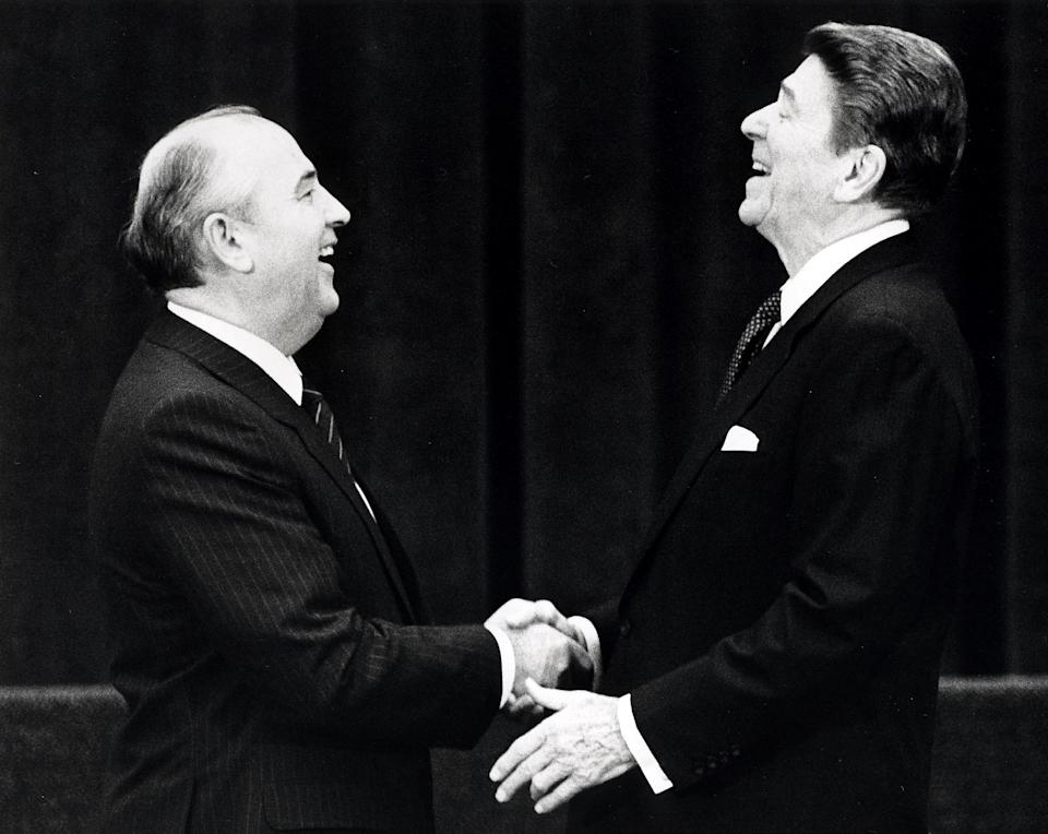 U.S. President Ronald Reagan (R) shakes hands at his first meeting with Soviet leader Mikhail Gorbachev to sign an arms treaty in Geneva, in this November 19, 1985 file photo. The two leaders met for the first time to hold talks on international diplomatic relations and the arms race. REUTERS/Denis Paquin/Files
