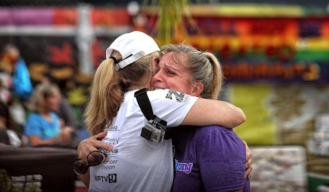 <p>Runners Randa Black, left, and Elizabeth Anne-Noles cry after stopping in front of the Pulse nightclub during the CommUNITYRainbowRun 4.9K road race, on Saturday, June 10, 2017, in Orlando, Fla. (Joe Burbank/Orlando Sentinel/TNS via Getty Images) </p>