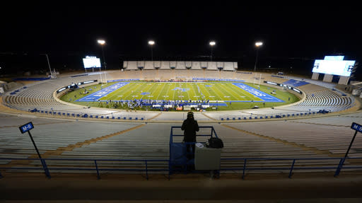 With no crowd in attendance to meet upgraded coronavirus restrictions put in place by the state, a videographer shoots as Air Force kicks the ball to New Mexico to start an NCAA college football game Friday, Nov. 20, 2020, at Air Force Academy, Colo. (AP Photo/David Zalubowski)