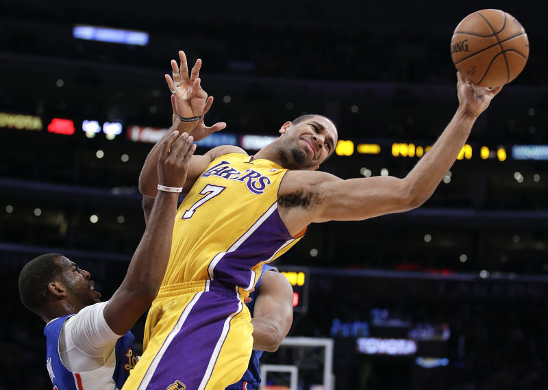 Los Angeles Lakers' Xavier Henry, center, passes the ball as he is defended by Los Angeles Clippers' Chris Paul during the first half of an NBA basketball game on Thursday, March 6, 2014, in Los Angeles. (AP Photo/Jae C. Hong)