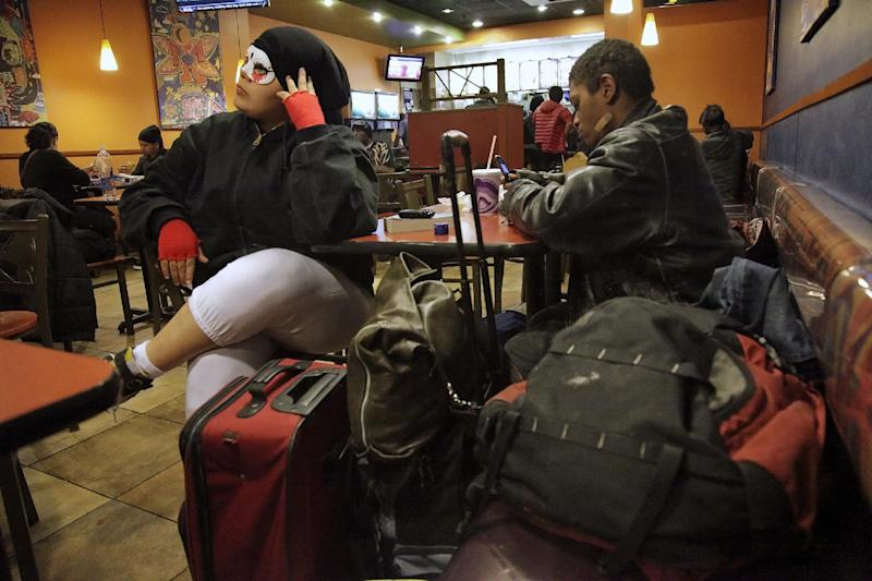 """Wearing a mask to protect her """"soul,"""" Gizmo Lopez, 19, left, who identifies herself as bisexual and homeless, sits with her boyfriend Tiny Jenkins and all their possessions inside a fast food restaurant, waiting to ride the subways for a night's sleep on Thursday, March 1, 2012,  in New York.  Almost half of the city's homeless youth are part of the LGBT - lesbian, gay, bisexual or transgender  population. (AP Photo/Bebeto Matthews)"""