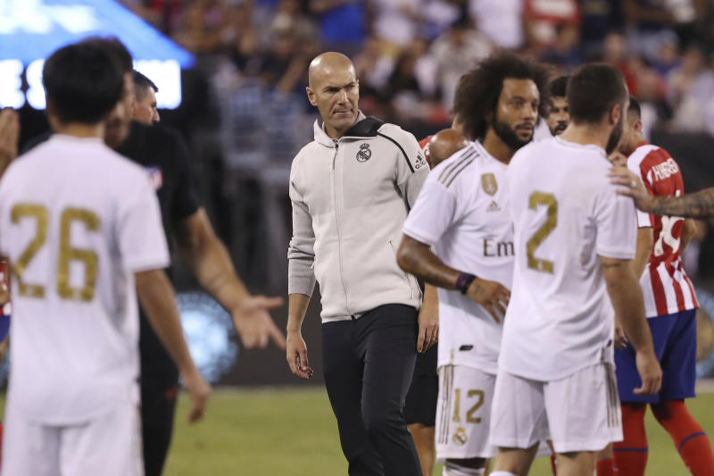 Real Madrid manager Zinedine Zidane, center, observes the scuffle on the pitch between Atletico Madrid and Real Madrid during the second half of an International Champions Cup soccer match, Friday, July 26, 2019, in East Rutherford, N.J. Atletico Madrid won 7-3. (AP Photo/Steve Luciano)