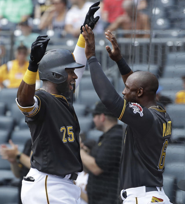 Pittsburgh Pirates' Gregory Polanco (25) is greeted by Starling Marte as he returns to the dugout after hitting a solo home run off Milwaukee Brewers starting pitcher Chase Anderson during the first inning of a baseball game in Pittsburgh, Saturday, July 14, 2018. (AP Photo/Gene J. Puskar)