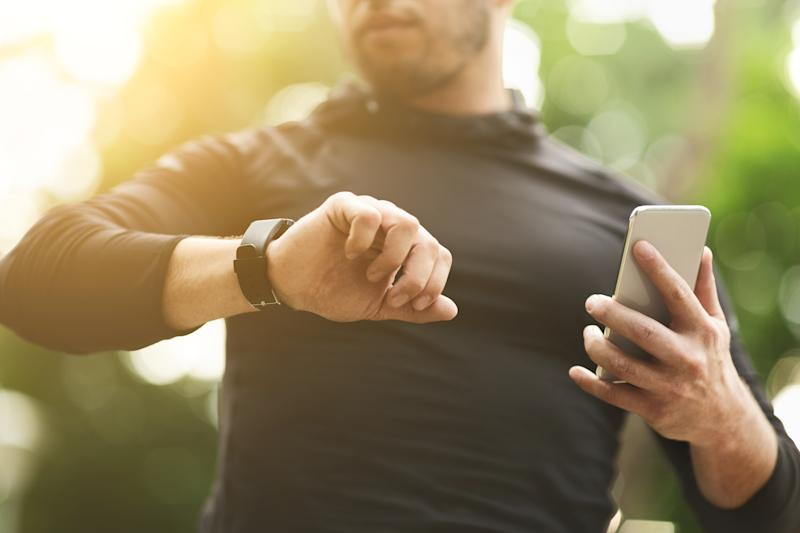 Closeup of unrecognizable man checking workout data on fitness tracker after intensive training outdoors, free space